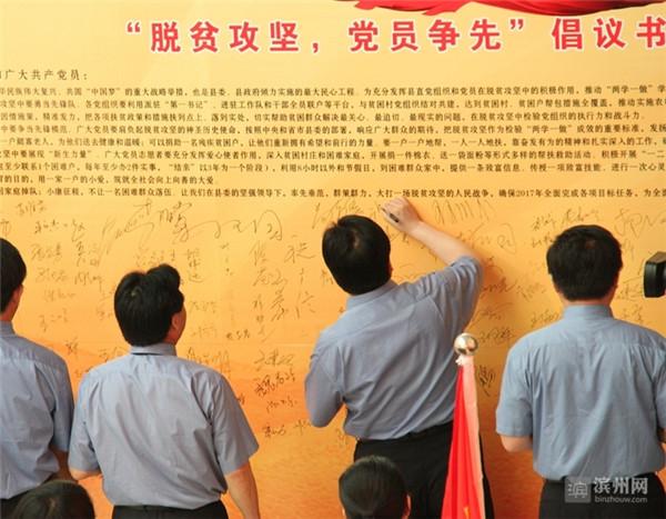 """阳信县组织党员在""""脱贫攻坚,党员争先""""倡议书展板上签名承诺"""