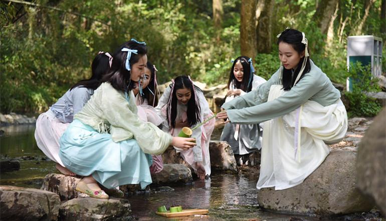 2018年4月17日,杭州,宋城千古情艺术团的美女演员在溪边曲水流觞、玩水嬉戏,再现了上巳节的传统习俗。