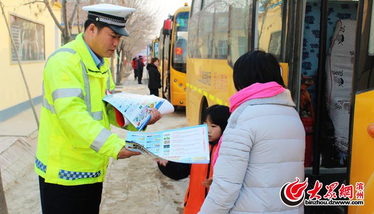 交警向学生家长发放交通安全宣传画,教育学生要掌握安全乘坐校车的安全知识.jpg