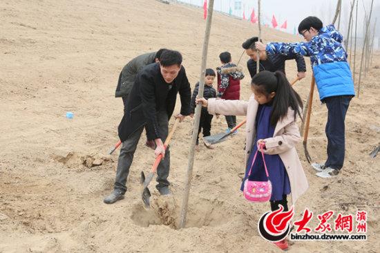 孩子们也上前帮忙植树。.jpg