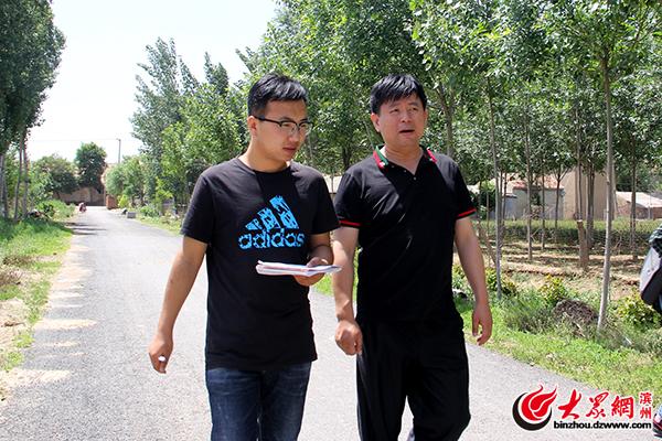 庞永祥(右)向记者介绍产业脱贫项目.jpg
